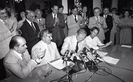Signing documents at press conference
